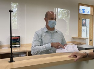 Man in Face Mask Using Social Distancing Counter Safety Screen