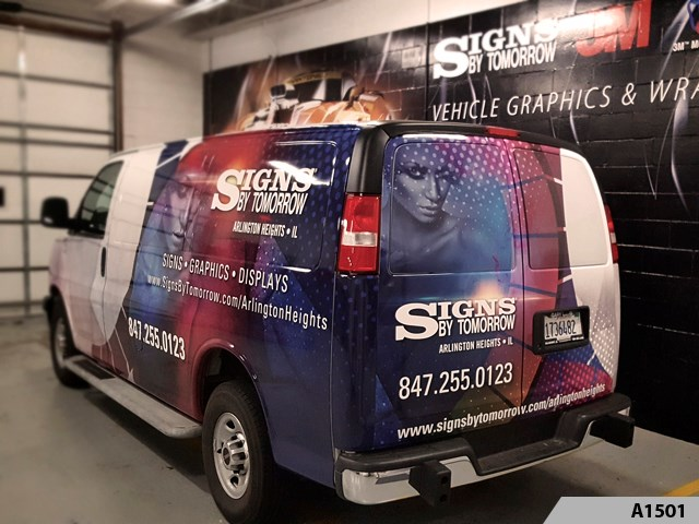 Our SBT Cargo Van fully wrapped, parked in our drive-in bay in front of large wall mural; vinyl graphics installed on cinder block wall.